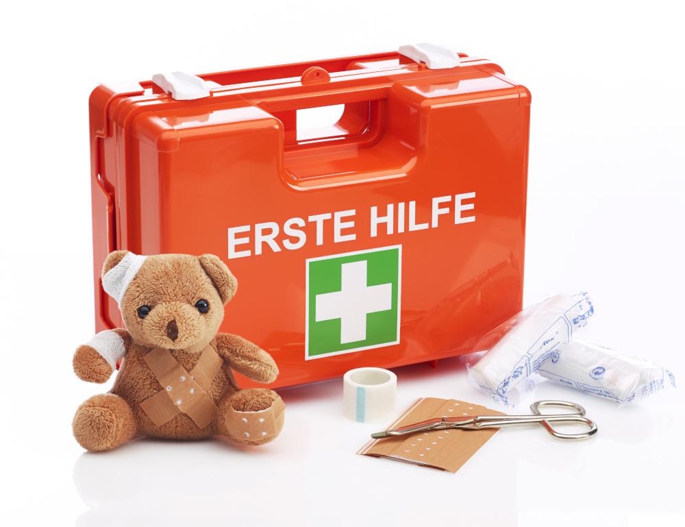 apteczka pierwszej pomocy obok narzędzia używane przy pierwszej pomocy plastry i pluszowy miś