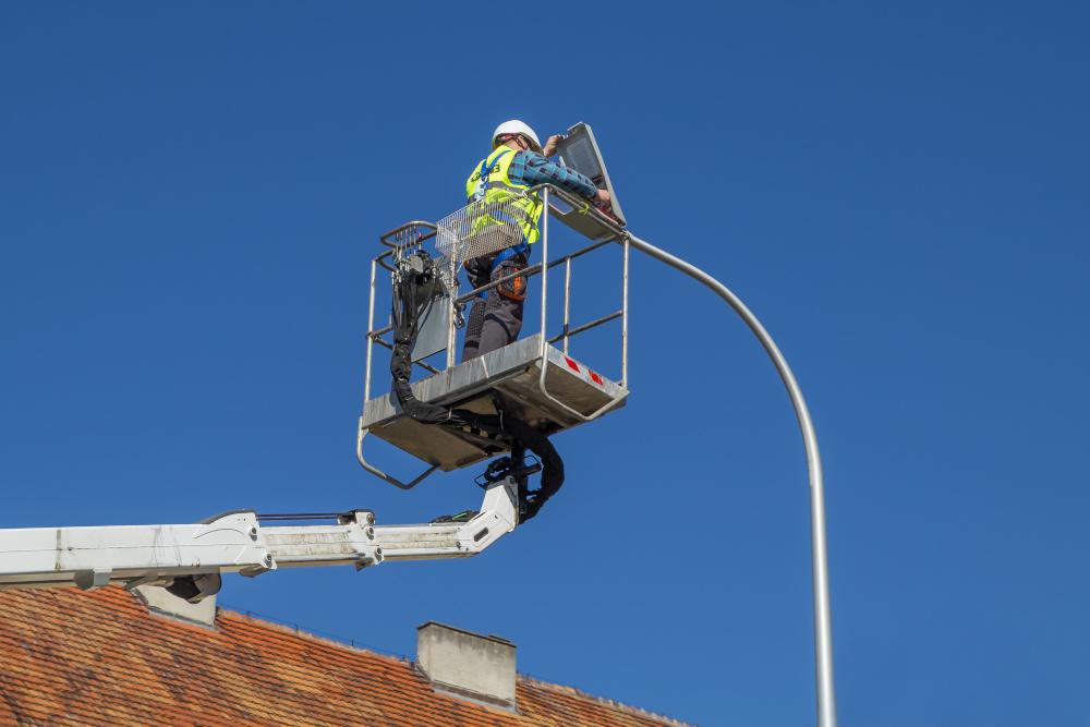 pracownik pracujacy na wysokosci podnoszony przez podnosnik koszowy